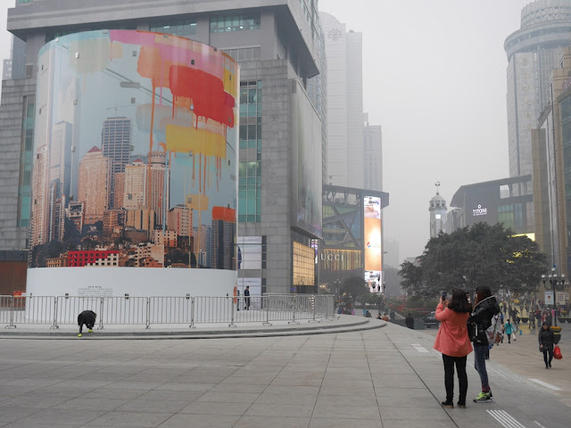People photographing mural by Navid Baraty and YangYang Pan covering entrance to Jiefangbei Apple Store in Chongqing