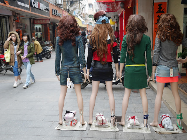 two young women walking past mannequins in Yangjiang, China
