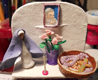 picture of the top shelf of a miniature handmade bookshelf with several Mexican Virgins and other traditional items