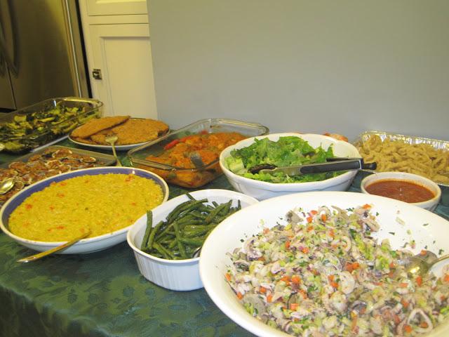 fish salad, risotto Milanese, string beans, green salad, fried calamari, baked clams, and bacalla in tomato sauce