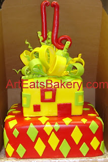 Two tier square yellow, red and green fondant sixteenth birthday cake with square and diamonds, and sugar bow