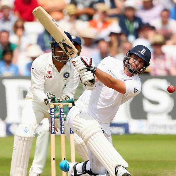 England's James Anderson (R) plays a shot during the fourth day of the first cricket Test match between England and India at Trent Bridge in Nottingham, central England on July 12, 2014.