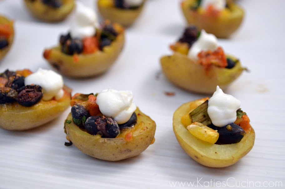 White tray filled with mini potato skins with corn, tomatoes, black beans and sour cream.
