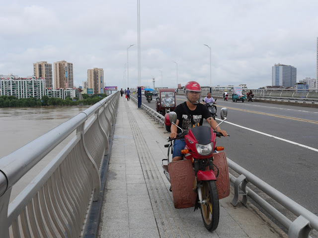 man riding a motorbike on a bridge's pedestrian sidewalk