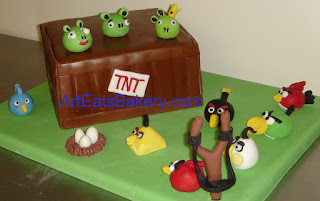 Angry Birds custom designed fondant birthday cake with TNT, sugar pigs, birds, eggs, nest, and slingshot