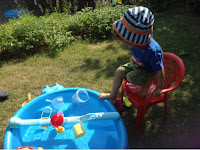 Blue hippo paddling pool, toys and toddler in sunhat