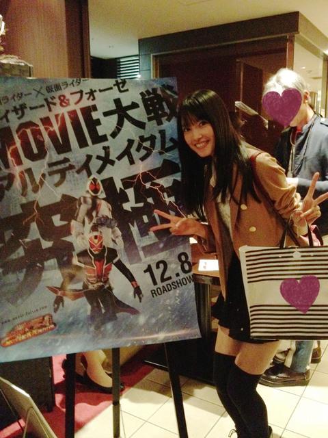 Nakayama Erina com o pôster do filme de Kamen Rider Wizard e Fourze.