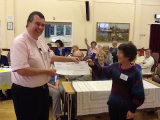Rev. Steve Mann presents a cheque from the estate of Bert Mitchell, which will be used for our new blue wheelchair van. November 2012