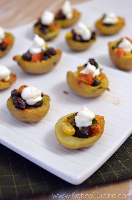 Long photo of sliced mini potatoes filled with beans and corn topped with sour cream.