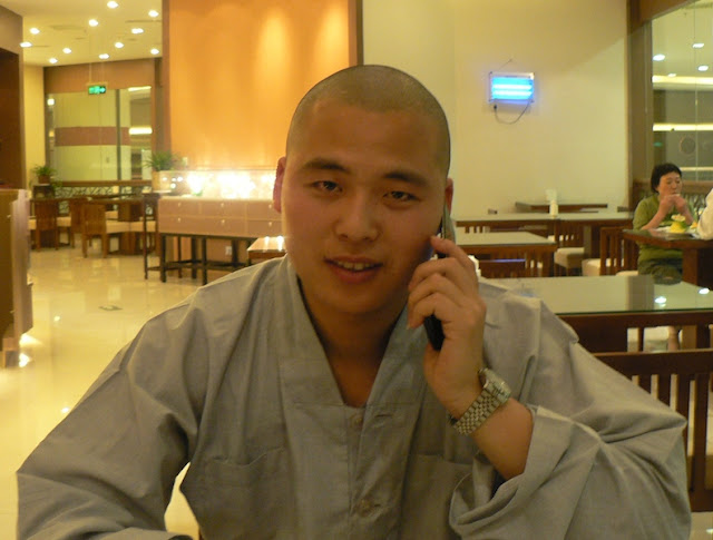 Buddhist monk talking on a mobile phone in Yangzhou, China