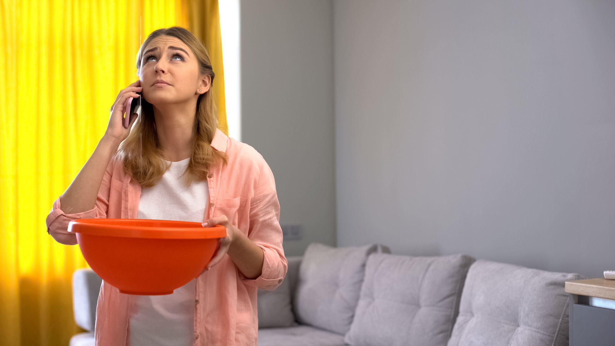 Woman looking at a leak in her ceiling while on the phone with a structural engineer.
