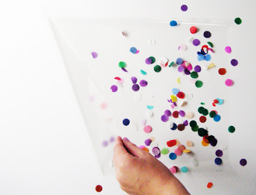 Take a piece of clear contact (the type you cover school books with) about double the size you want your bow to be. Peel the contact paper open and sprinkle one half with confetti pieces.