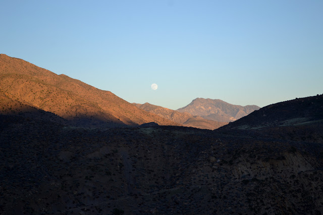 moon rising above a few still lit mountains