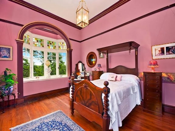 This room has Federation features such as the minimal cornice, timber picture rails, gothic coloured glass panels above the casement windows, polished floor boards and Federation chest of drawers. The curvy wooden bed with barley twist corners is Victorian in style. Notice the classic porthole window, a Federation feature derived from the work of English Queen Anne architect Norman Shaw.