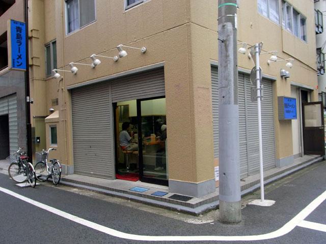 青島食堂のお店の外観。シャッターが半分閉まっているが、ちゃんと営業中です。