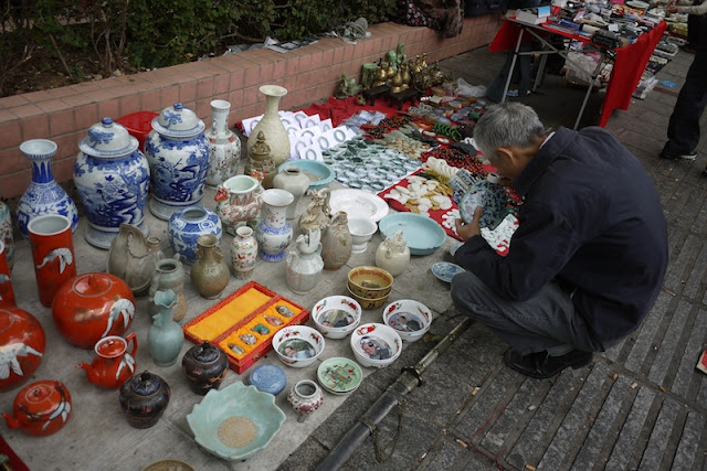 man closely examining a vase outside Tianxinge Antique City in Changsha, China