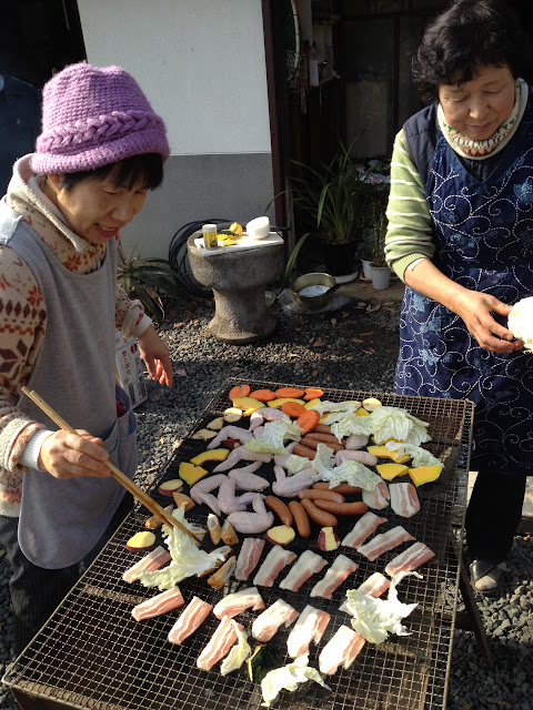 Mrs. Sugita turns food on the grill