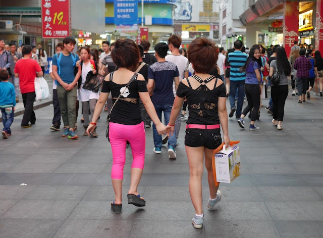 young women wear black a hot pink outfits and holding hands