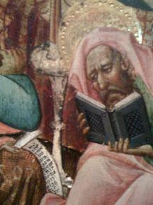 Sabio o santo leyendo un libro y pergamino.