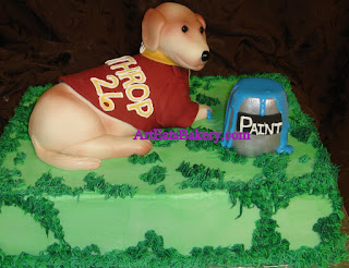 Custom unique Groom's cake with edible dog sculpture wearing a Wintrop  baseball jersey and playing in a paint can