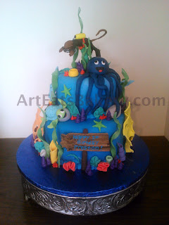 Custom creative two tier kids birthday cake with fondant octopus, scuba diving monkey, coral life, turtle and wood plank sign.