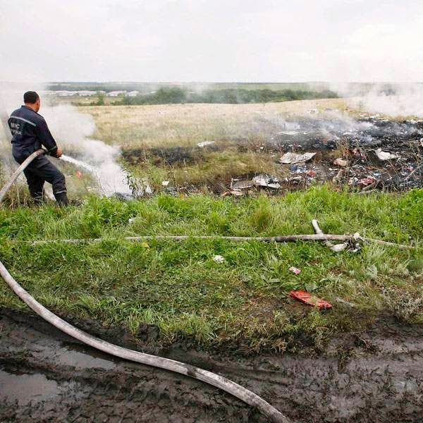Emergencies Ministry member works to put out a fire at the site of a Malaysia Airlines Boeing 777 plane crash in the settlement of Grabovo in the Donetsk region, July 17, 2014.