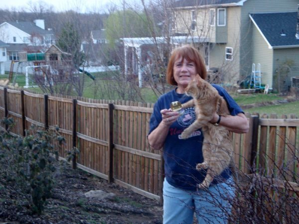 my mom holding Merlin with one arm and a can of open cat food in the other hand