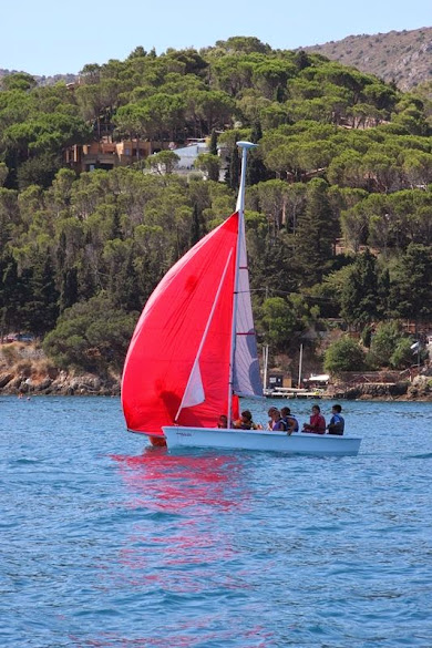 Sailing boat with kids and red sail near the coast of Monte Argentario