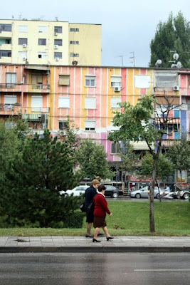 Women walking in front of a colorful communist building in Tirana