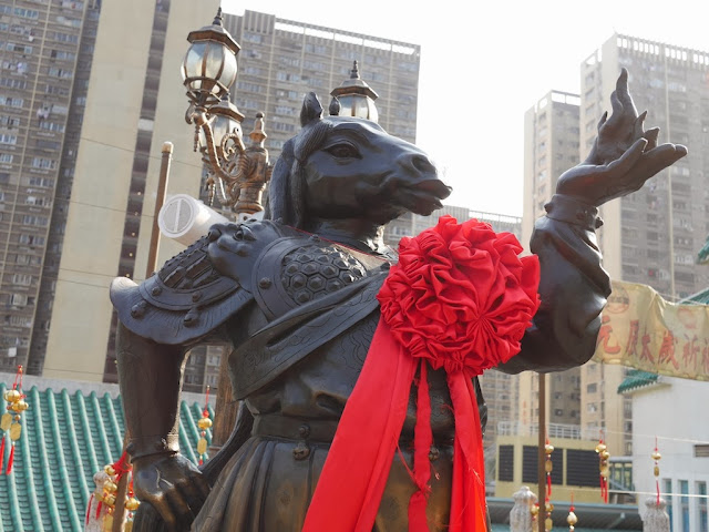 statue of a human figure with a horses head in traditional Chinese armor holding a flame