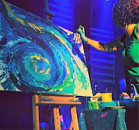 Live Painting: a woman paints on stage during a live event