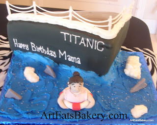 Titanic ship custom creative birthday cake design with lady in lifesaver, water, icebergs and shark fins