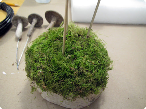 13. Cover the top of the wood with white glue and preserved moss for final touches. It helps to stick screwers in the holes to remember exactly where they are. Remove them when glue is dry and place mushrooms on the grassy knoll.