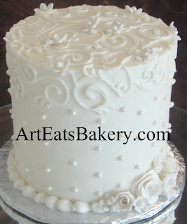 Tall tier white butter cream romantic elegant wedding cake with royal icing curlicues, sugar pearls and edible flowers design