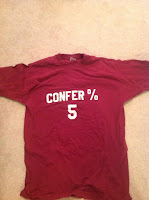 Photo of the front of a CONFER % 5 t-shirt