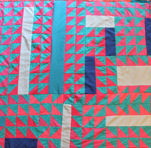 a quilt made of lots of pink and blue triangles