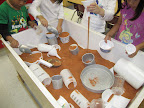 Children scoop, pour, and measure dry sand in a sensory table.