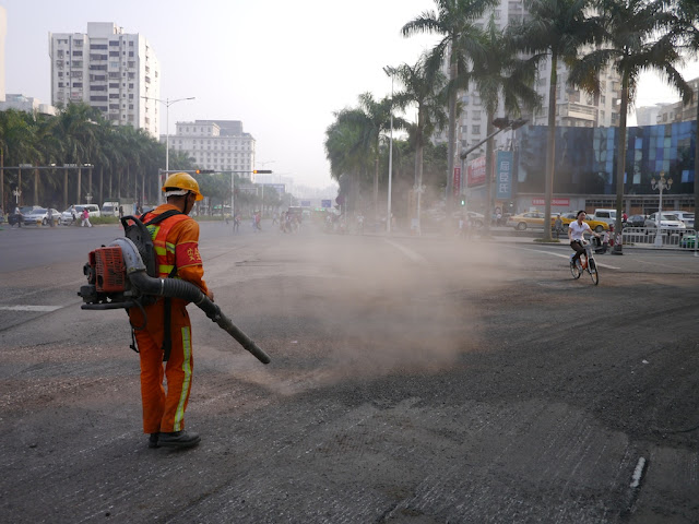 bicyclist going through a cloud of dust caused by a man blowing graving on a street in Zhuhai
