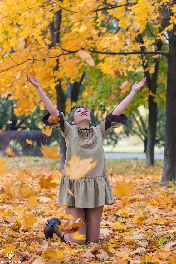 Красивая осенняя фотосессия в парке - девушка бросает осенние листья