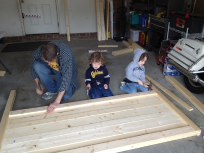 An in progress picture of a man and two boys making a wood headboard