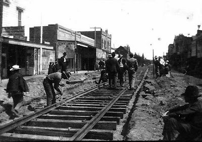 1831 - Railroad workers laying rails of interurban Petaluma & Santa Rosa Electric Railway  down Main Street Sebastopol circa 1904.