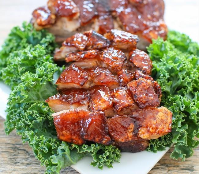 slices of crispy pork belly on a serving platter with lettuce leaves