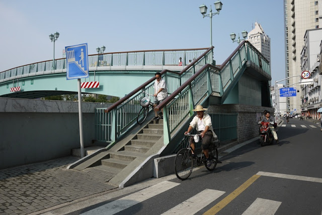 man walking bike down ramp on pedestrian bridge in Shanghai