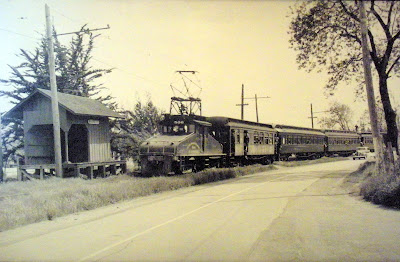 1824 - P&SR train  at the Bassett Station (close to Fredericks Road) south of  Sebastopol.  Engine 506 is pulling four passenger cars with many people hanging out the windows of the cars and a line of 1930's autos on the road next to the train.   Since the P&SR ended passenger service in the early 1930's, this may have been one of the final runs carrying passengers.