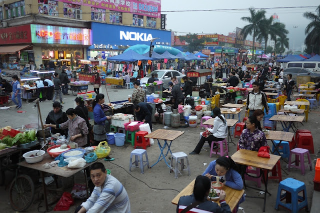 numerous small tables for eating alongside a shopping street in Nanping, Zhuhai