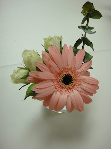 Simple arrangement with a pink daisy and white spray roses
