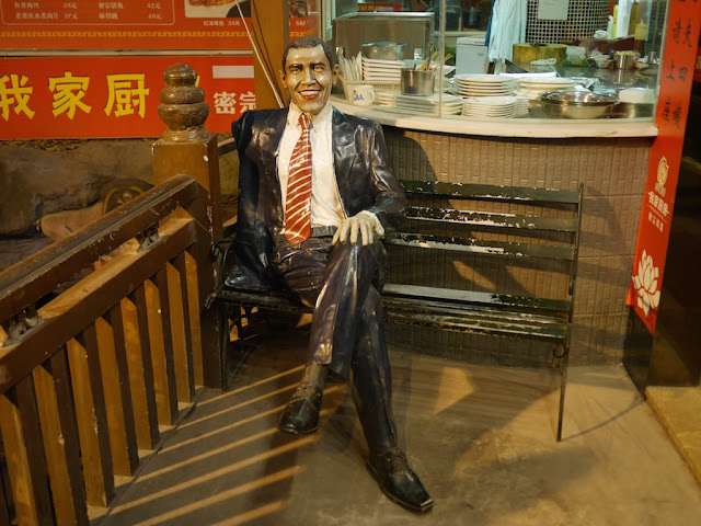 A Barack Obama statue sitting on a bench