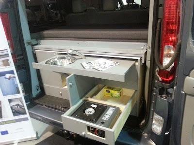 Na zdjęciu zabudowana kuchnią ze zlewem przestrzeń tylnia busa