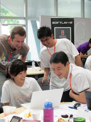 'Huddling around, enjoying the fruits of labour' by Startup Weekend Singapore