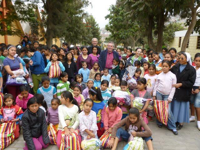 Grupo Sembradores de Amor dándoles ropa a las niñas